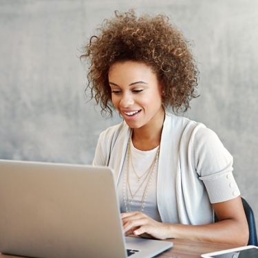Lady with curly hair working on laptop